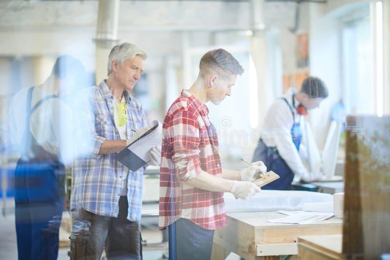 Kontrollejunger arbeitnehmer des ernsten Vorarbeiters stockbild