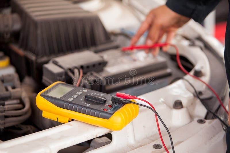 Kontrollera batteriet av en bil arkivfoto
