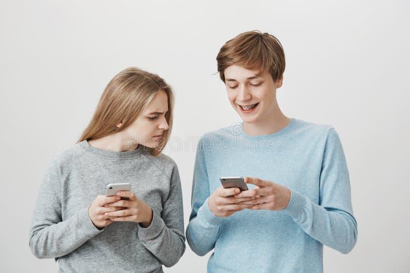 Kontrollera för flickvän vem är den flickapojkvänmessaging med Stående av den fokuserade lynniga kvinnan, rynka pannan som rymmer arkivfoton