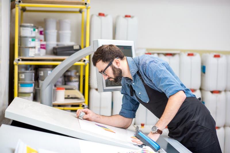 Kontrollera kvaliteten av printingen med förstoringsglaset arkivbild