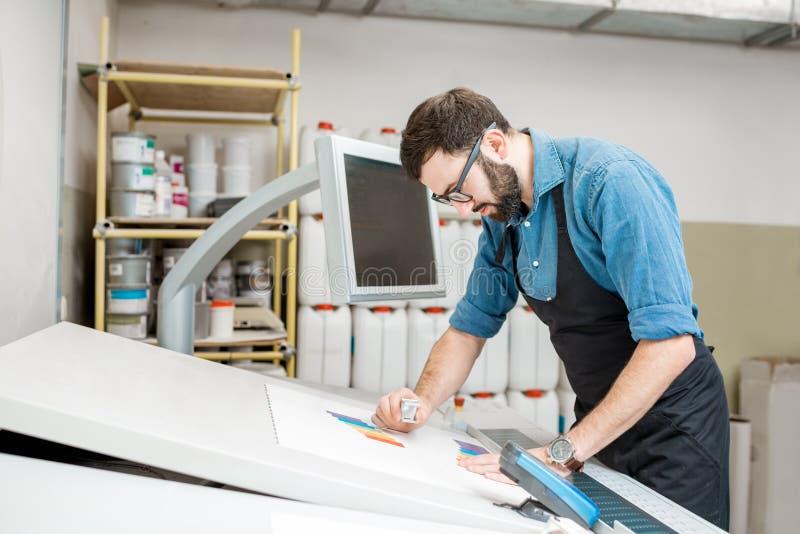 Kontrollera kvaliteten av printingen med förstoringsglaset royaltyfri fotografi