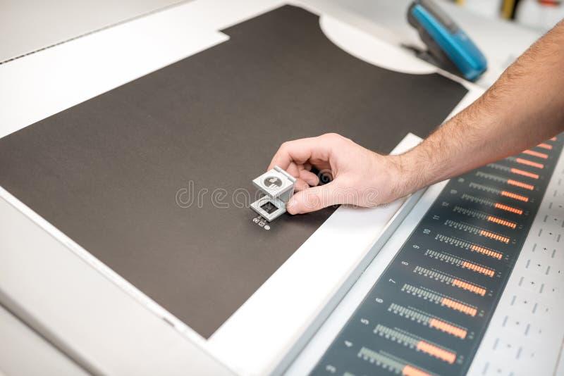 Kontrollera kvaliteten av printingen med förstoringsglaset royaltyfri bild