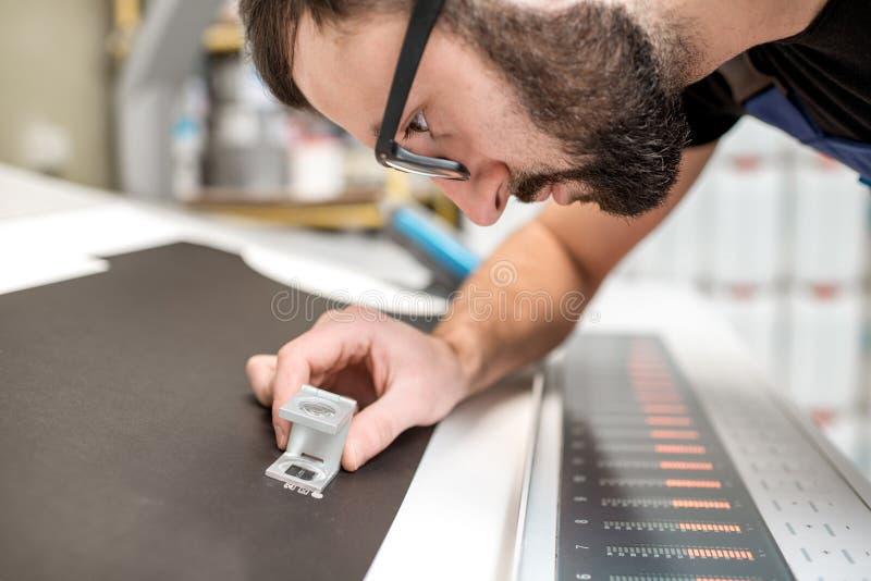 Kontrollera kvaliteten av printingen med förstoringsglaset royaltyfria foton