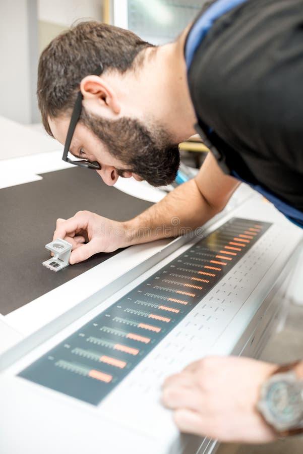 Kontrollera kvaliteten av printingen med förstoringsglaset arkivbilder
