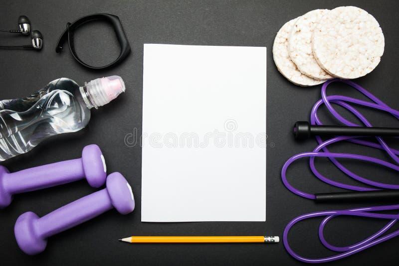 Kontrollera listan med kopieringsutrymme med konditionutrustning Sund livsstil, idrottshall- och genomkörarebegrepp på svart bakg royaltyfria foton