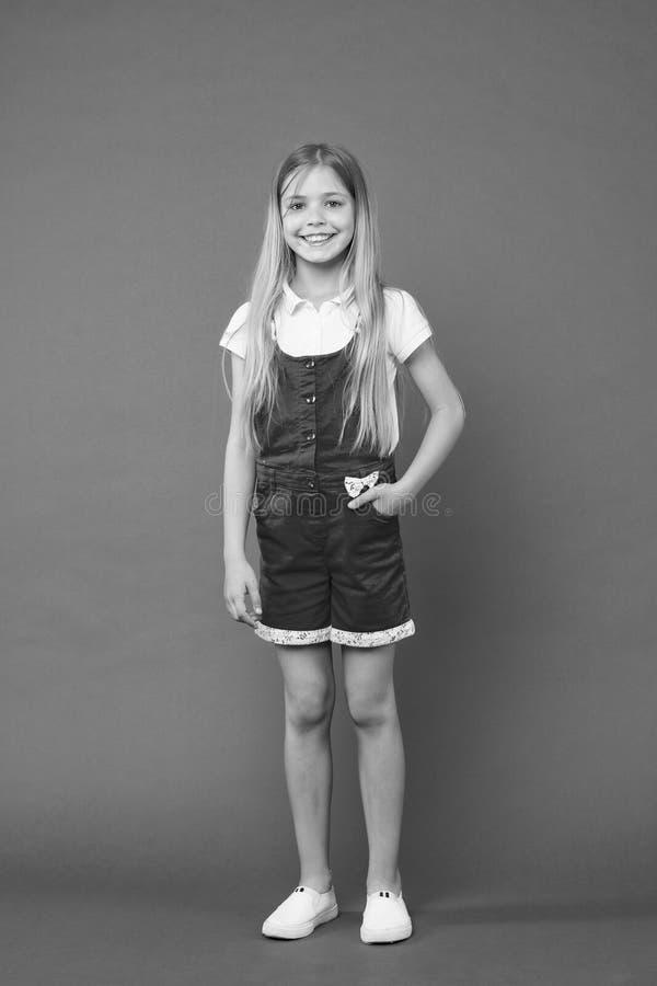 Kontrollera ut min dräkt Tonårmodebegrepp Lycklig le framsida för flicka som poserar stilfulla overaller, violett bakgrund Ungefl royaltyfria bilder
