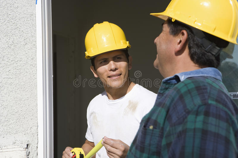 Kontrollerande fönster för två byggnadsarbetare royaltyfria foton