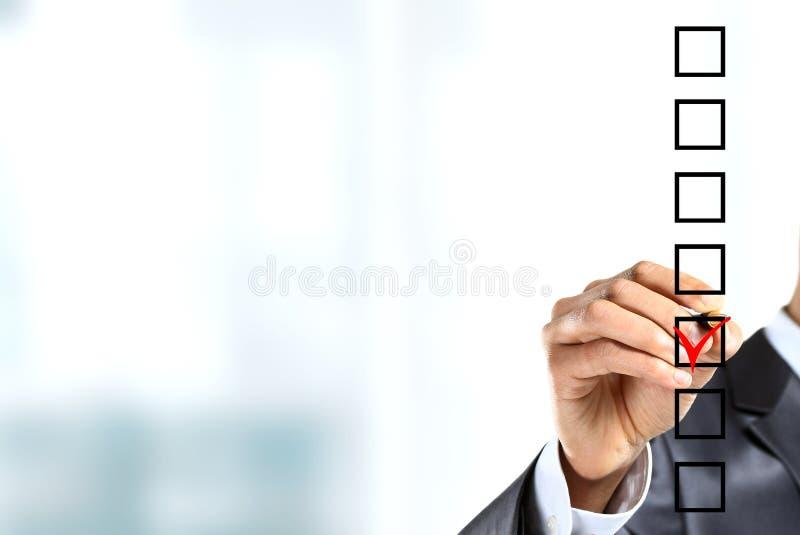 Kontrollerande fläck för ung affärsman på kontrollista med markören fotografering för bildbyråer