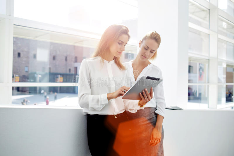 Kontrollerande lista för två lyckade affärskvinnor av angelägenheter på den digitala minnestavlan, medan stå i regeringsställning royaltyfria bilder