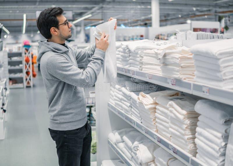 Kontrollerande och köpande handdukar för manlig kund i supermarket royaltyfria foton