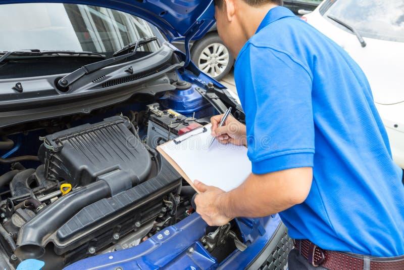 Kontrollerar den hållande skrivplattan för mekanikermannen och bilen arkivbilder