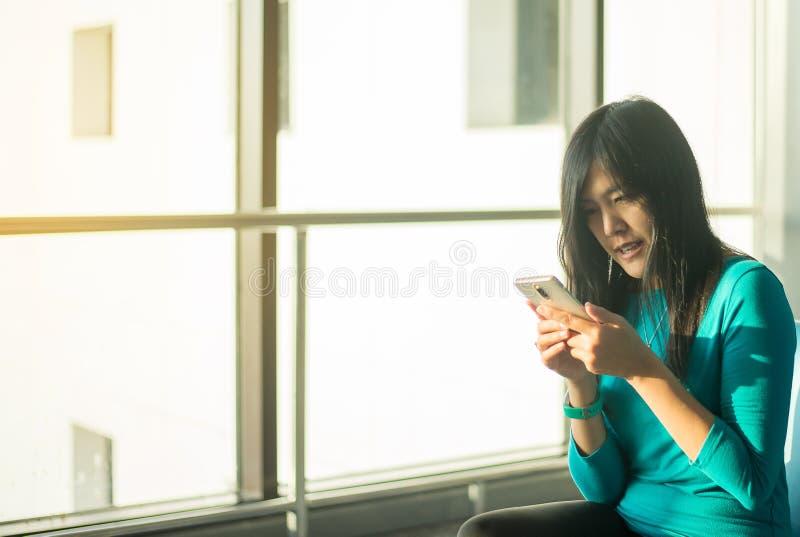 Kontrollerar reser den hållande mobiltelefonen för den asiatiska kvinnapassageraren och det kontrollerande flyget eller online- i fotografering för bildbyråer
