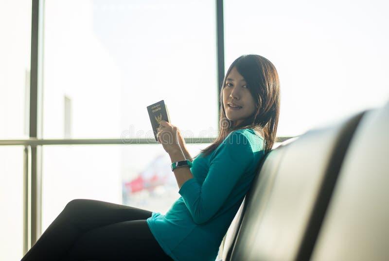 Kontrollerar reser det hållande passet för den asiatiska kvinnapassageraren och det kontrollerande flyget eller online- in och st arkivbilder