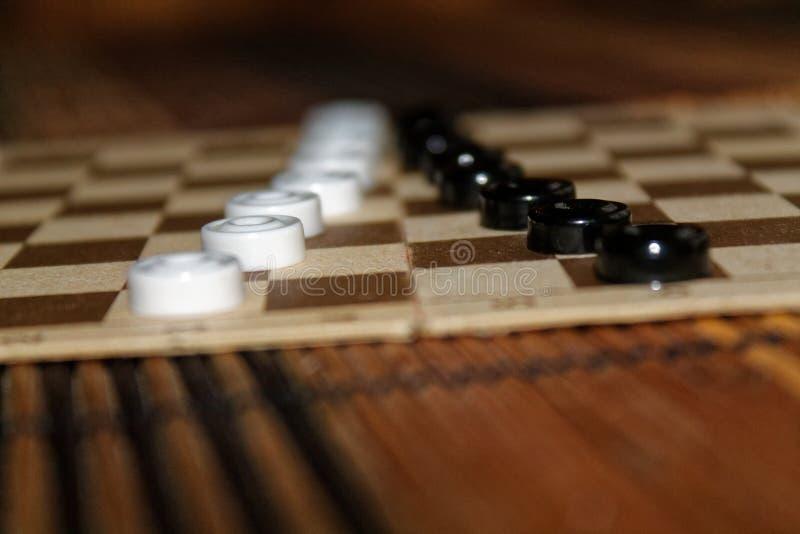 Kontrolleure im Schachbrett bereit zum Spielen Abstrakte Abbildung 3d Ein altes Spiel liebhaberei Kontrolleure auf dem Spielfeld  lizenzfreie stockfotos