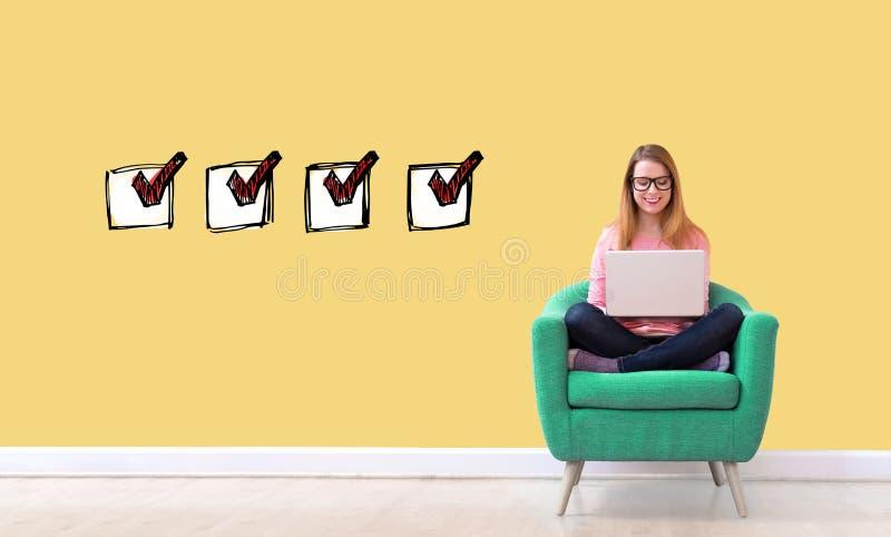 Kontrollista med kvinnan som anv?nder en b?rbar dator royaltyfri foto