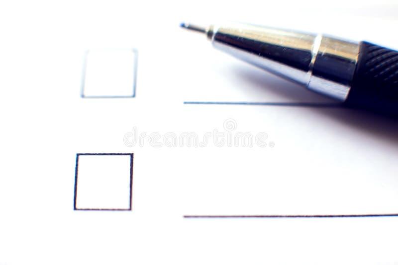Kontrollistaform med en penna på vitbok Checkboxbegrepp royaltyfria foton