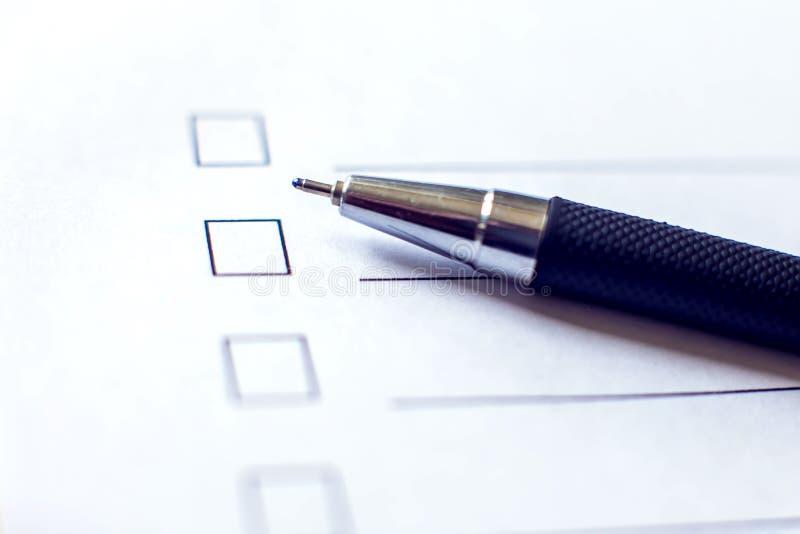 Kontrollistaform med en penna på vitbok Checkboxbegrepp royaltyfri foto