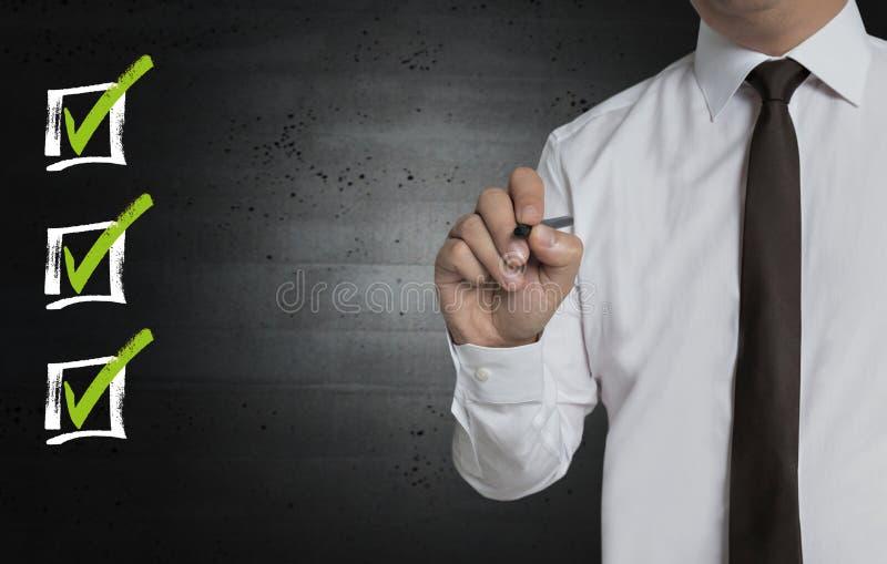Kontrollistan är skriftlig vid affärsmannen på skärmen arkivfoto