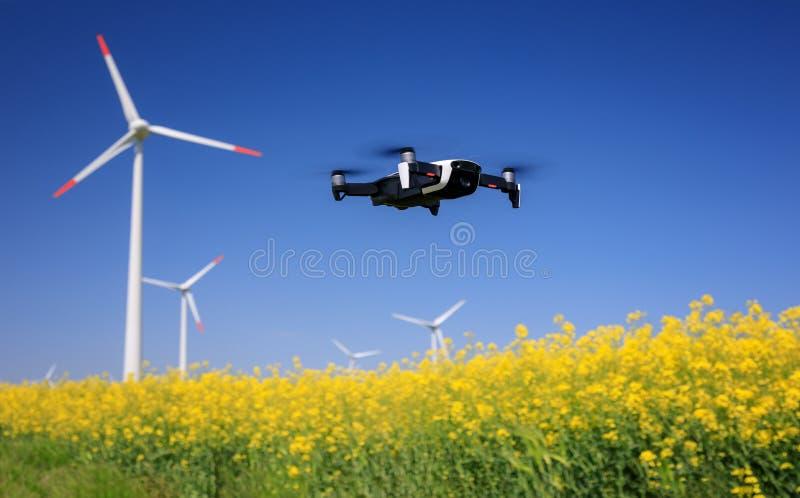 Kontrollsurr med eolian turbiner bakom Rapeseedf?lt i blom f?rnybar energi arkivfoto