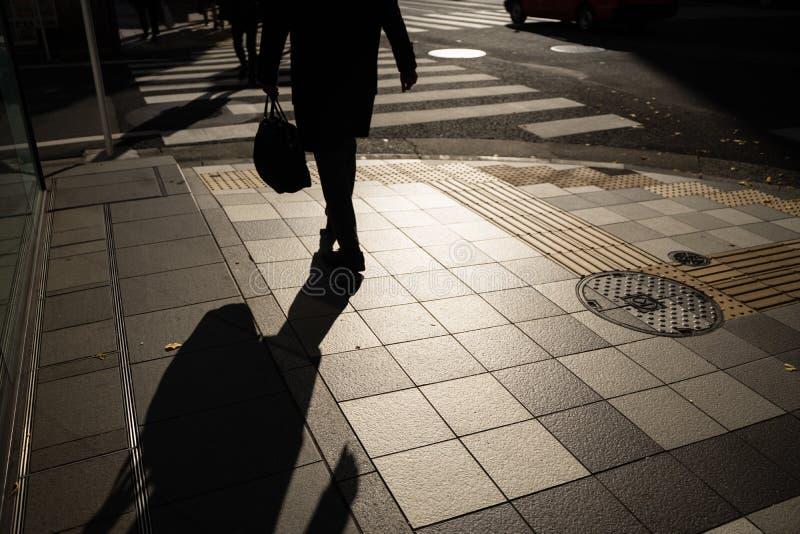 Kontur av affärsmannen, påse för kontorsgrabbinnehav som går för att arbeta i morgonen i Tokyo, Japan royaltyfria bilder
