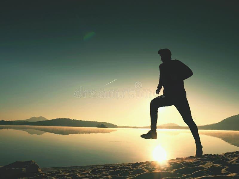 Kontur av aktiv idrottsman nenlöparespring på soluppgångkust Sund livsstilövning för morgon arkivbild