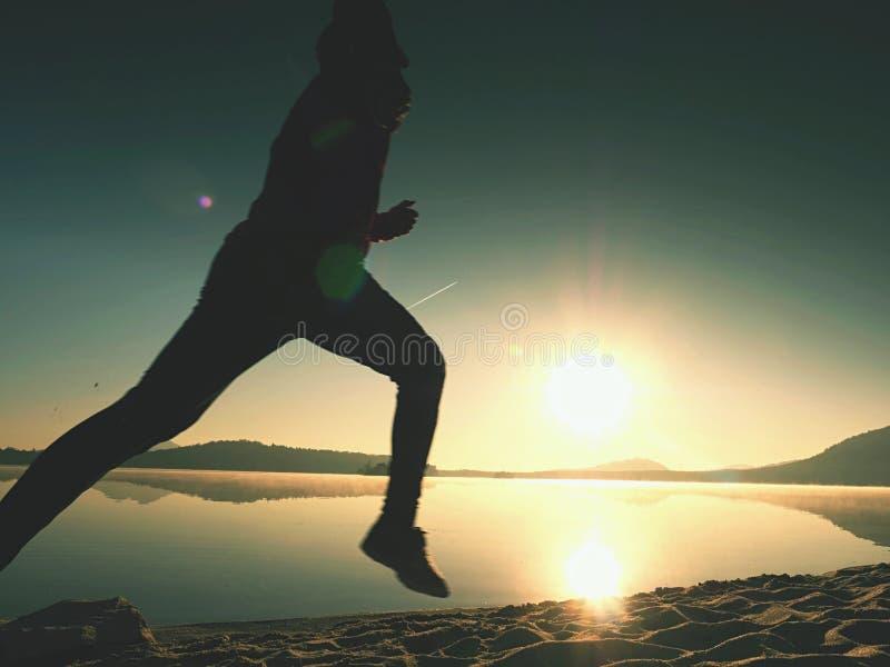 Kontur av aktiv idrottsman nenlöparespring på soluppgångkust Sund livsstilövning för morgon royaltyfria foton
