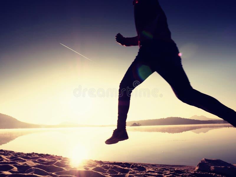 Kontur av aktiv idrottsman nenlöparespring på soluppgångkust Sund livsstilövning för morgon fotografering för bildbyråer