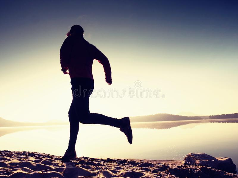 Kontur av aktiv idrottsman nenlöparespring på soluppgångkust Sund livsstilövning för morgon arkivfoto