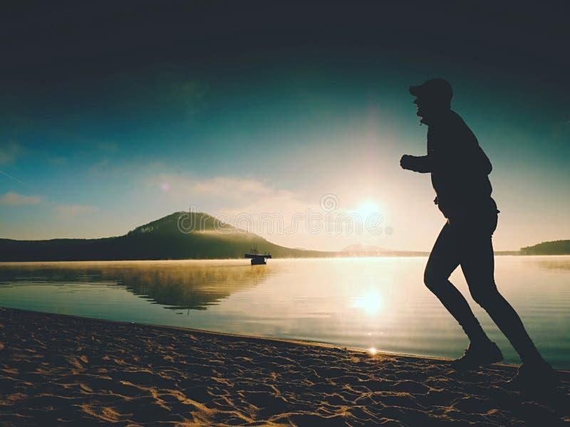 Kontur av aktiv manspring för sport på sjöstranden på soluppgång Sund livsstil arkivfoto