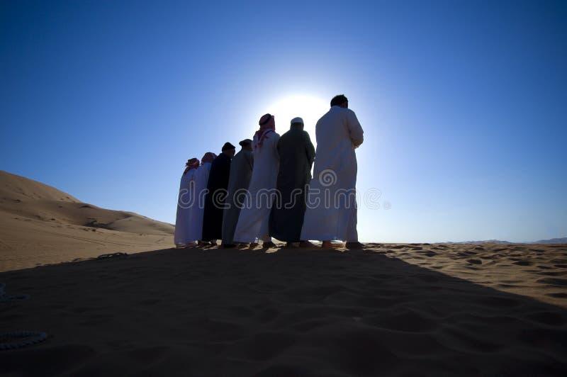 Kontur av arabiska män som ber Asr i öknen arkivbilder