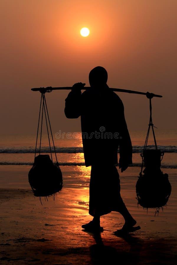 Kontur av arbetaren som går på stranden under solnedgång royaltyfria bilder