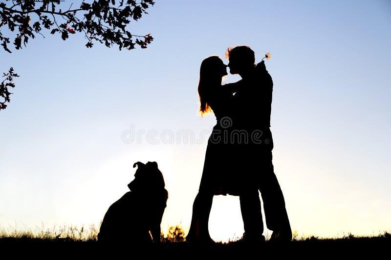 Kontur av att älska barnpar som kramar under träd på solnedgången arkivbilder