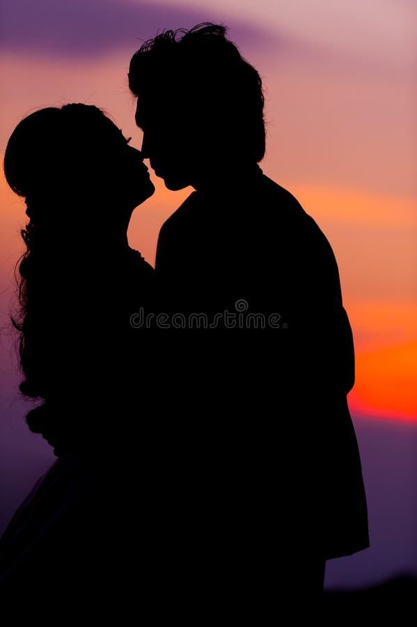 Kontur av att omfamna den asiatiska bruden och brudgummen på solnedgången royaltyfri bild