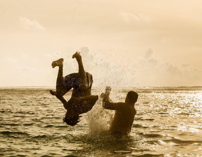 Kontur av banhoppningen för ung man ut ur havet royaltyfri bild