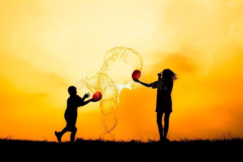 Kontur av barn som spelar vatten under himmelsolnedgång arkivbilder