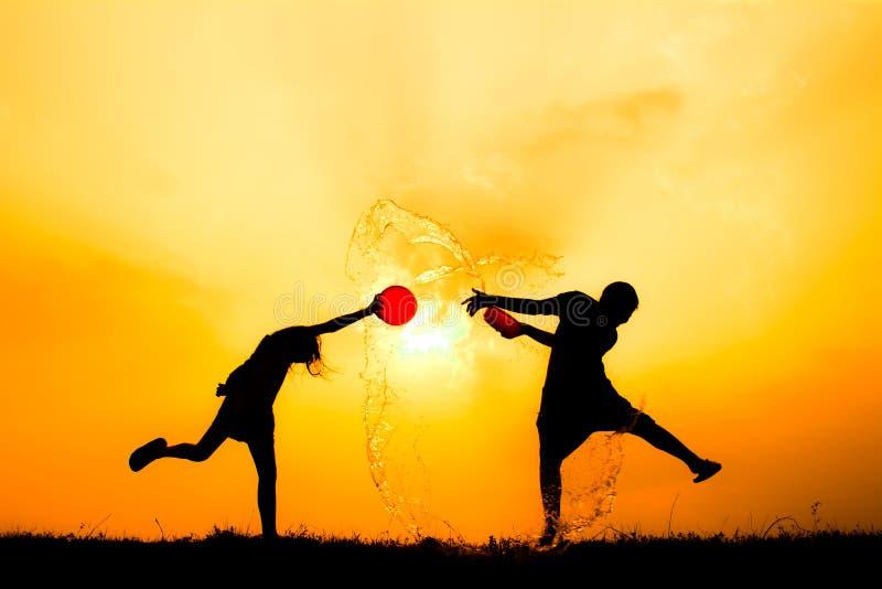 Kontur av barn som spelar vatten under himmelsolnedgång royaltyfri fotografi