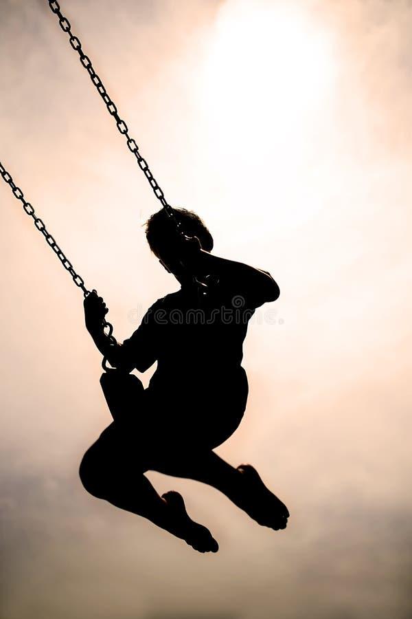 Kontur av barnet som svänger på PLaygroung Swingset arkivbild