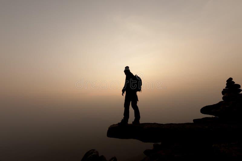 Kontur av berget för manframgång överst på solnedgången som är selektiv arkivbild