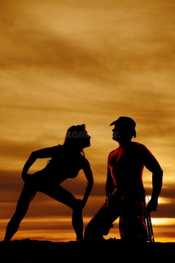 Kontur av cowboy- och kvinnaslutet i solnedgång arkivbild