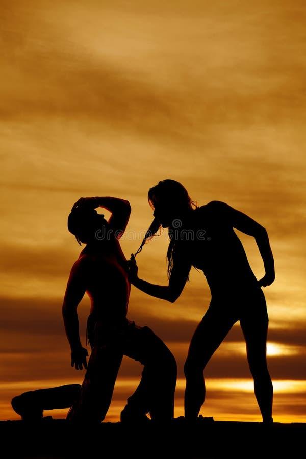 Kontur av cowboyen som knäfaller vid kvinnan i solnedgång royaltyfri foto