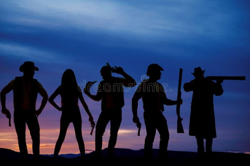 Kontur av cowboyer i solnedgång med vapen arkivbilder