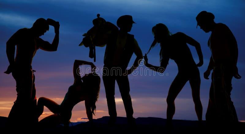 Kontur av cowboyer och kvinnor i solnedgången royaltyfri fotografi
