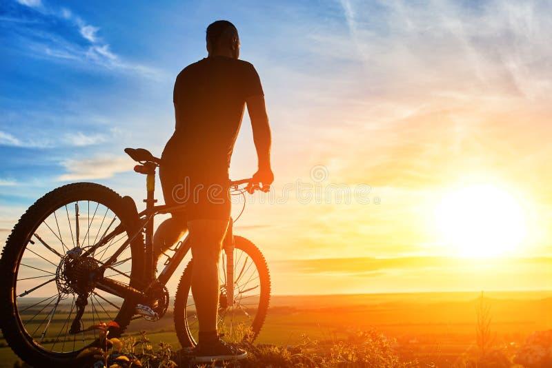 Kontur av cyklistanseendet med mountainbiket på kullen på solnedgången arkivfoto