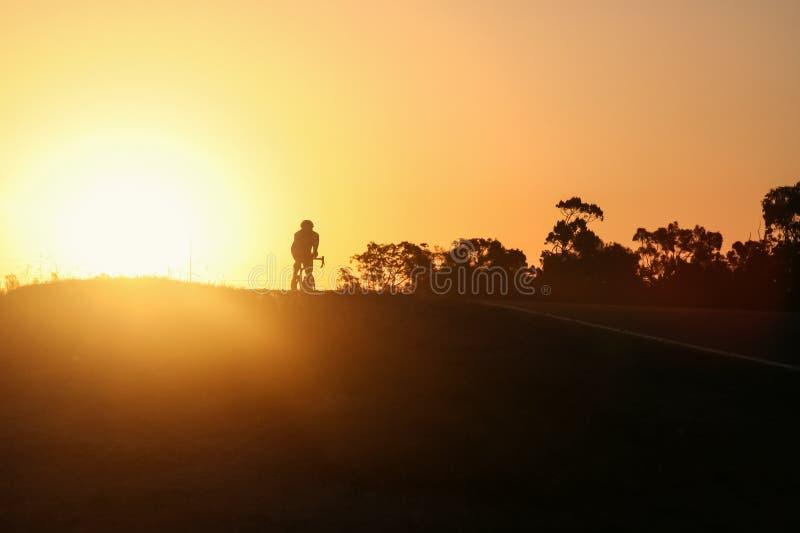 Kontur av cyklisten med en apelsin och en gulinghimmel royaltyfri bild