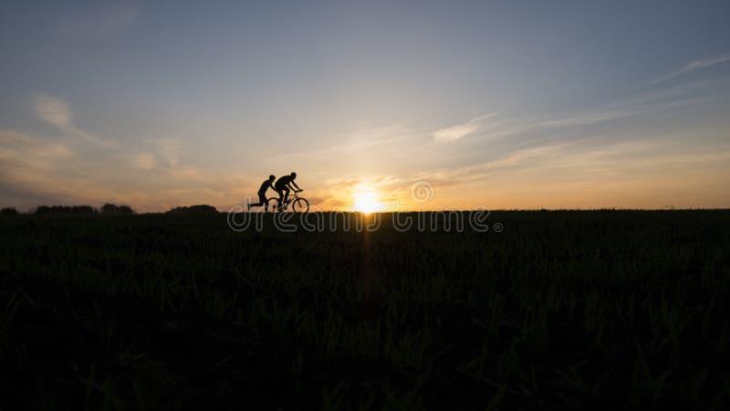 Kontur av cyklisten och den rinnande mannen utan cykeln i rörelse på bakgrunden av den härliga solnedgången Manlig push en cyklis arkivfoto