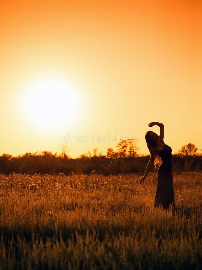 Kontur av dansunga flickan i klänning mot solnedgånghimlen arkivbilder