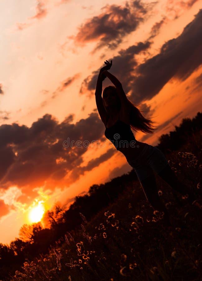 Kontur av dansunga flickan mot solnedgånghimlen fotografering för bildbyråer