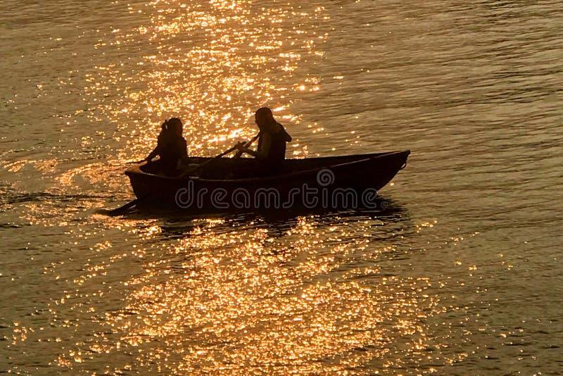 Kontur av datummärkningpar, fritids- fartyg på sjön på solnedgången arkivfoto