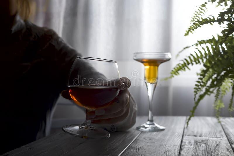 Kontur av den anonyma alkoholiserade kvinnapersonen som dricker bak exponeringsglas av alkohol Alkoholböjelse och samkvämproblem  royaltyfria foton