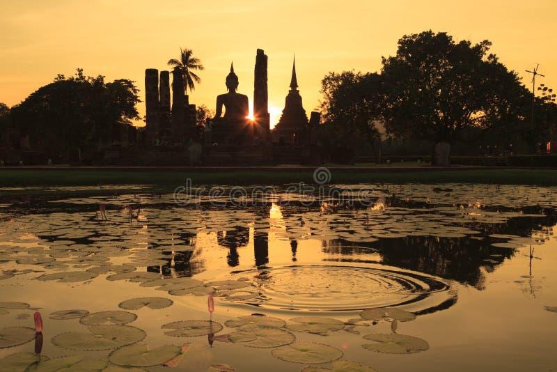 Kontur av den forntida Buddhastatyn och pagoder mot solnedgånghimmel på Sukhothai, Thailand royaltyfri foto